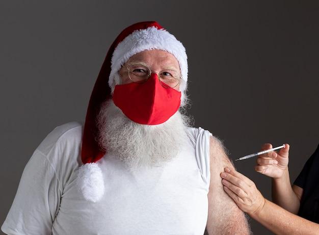Kerstman met gezichtsmasker wordt gevaccineerd met injectie