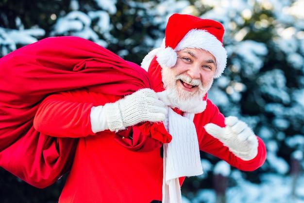 Kerstman met grote zak. gelukkig nieuwjaar. santa magische mist wandelen langs het veld. kerstman