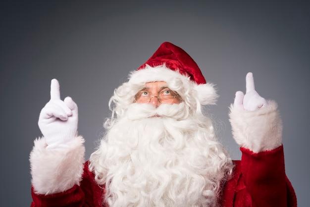 Kerstman met handen die de bovenste richting tonen