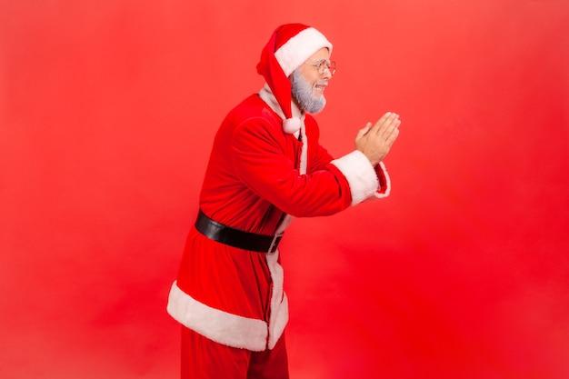 Kerstman met handen in gebed, smekende uitdrukking, smekend om hulp, vergeving vragend.