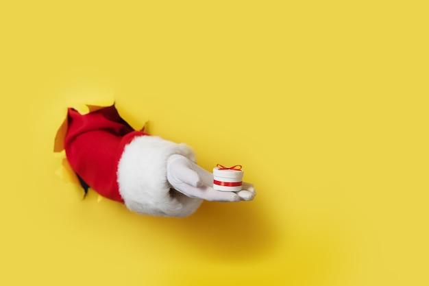 Kerstman met kleine geschenkdoos in zijn hand geïsoleerd over geel - alleen hand en arm