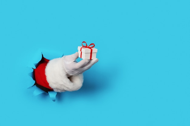 Kerstman met kleine geschenkdoos in zijn hand geïsoleerd over lignt blauw - alleen hand en arm