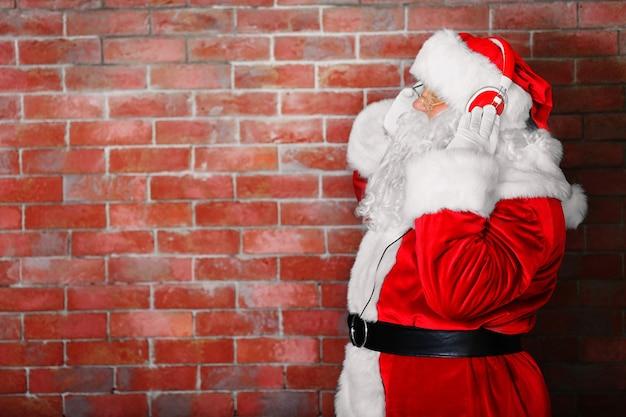 Kerstman met koptelefoon luisteren naar muziek op bakstenen muur achtergrond