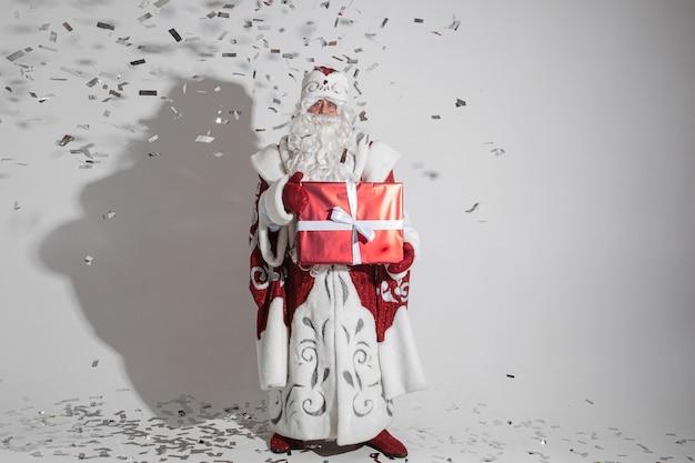 Kerstman met lange witte baard met grote rode doos met een kerstcadeau in zijn handen, foto geïsoleerd op een witte muur