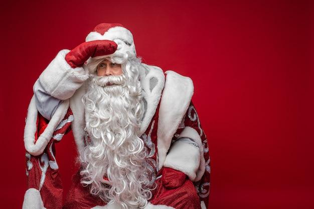 Kerstman met lange witte baard probeert iemand te zien, foto geïsoleerd op rode muur