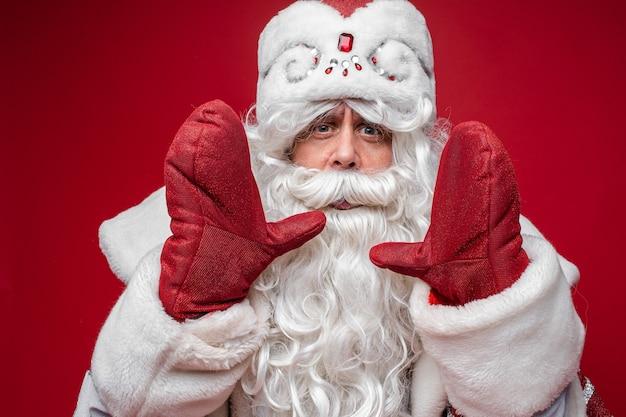 Kerstman met lange witte baard roept iemand, foto geïsoleerd op rode muur