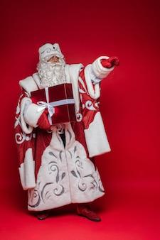 Kerstman met lange witte baard toont iets met zijn hand en houdt een cadeau, foto geïsoleerd op rode muur