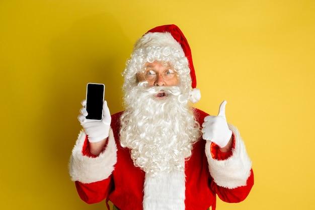 Kerstman met moderne bril geïsoleerd op gele studio achtergrond
