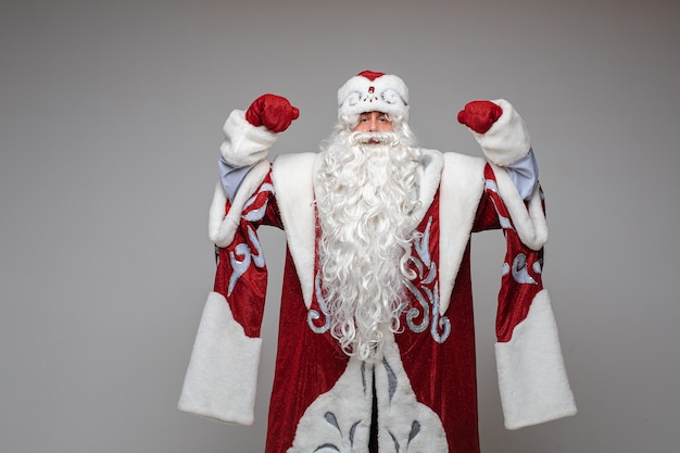 Kerstman met opgeheven handen in rood kostuum Gratis Foto