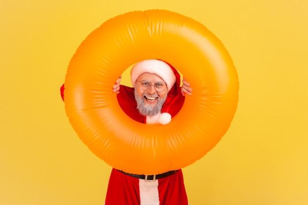Kerstman met oranje rubberen ring in handen, kijkend naar camera met vrolijke uitdrukking