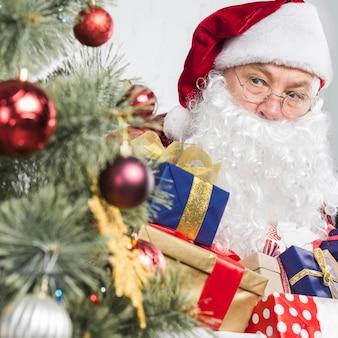 Kerstman met presenteert in handen in de buurt van de kerstboom