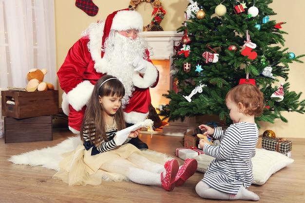 Kerstman met twee kleine schattige meisjes in de buurt van open haard en kerstboom thuis