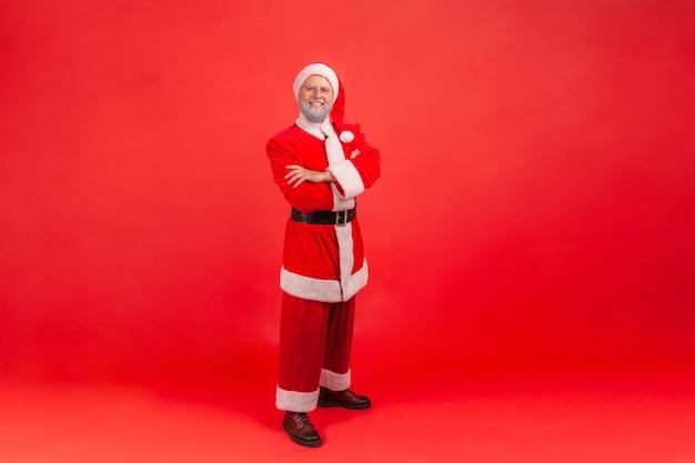 Kerstman met zelfverzekerde blik, staande met gevouwen armen en kijkend naar de camera.