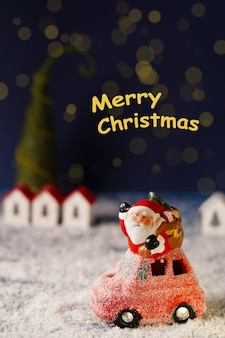 Kerstman op een rode auto op de achtergrond van kleine huizen en een kerstboom de inscriptie merr...