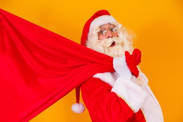 Kerstman op gele achtergrond met zak met geschenken met vrije ruimte voor tekst achter zijn rug. kerst campagnes