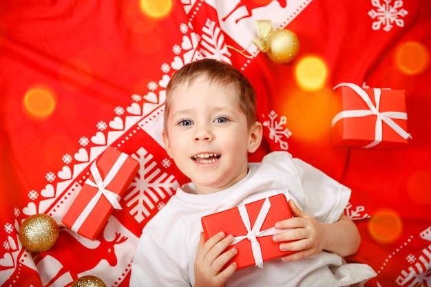 Kerstman peuter liggend op zijn rug met kerstcadeau
