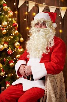 Kerstman portret, zittend binnen in de buurt van versierde kerstboom wi