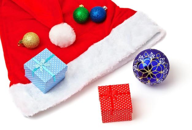 Kerstman rode en witte hoed, speelgoed bubbels en kerstcadeaus op witte achtergrond.