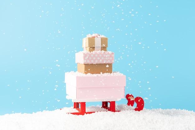 Kerstman slee met geschenkdozen onder sneeuwval op blauw