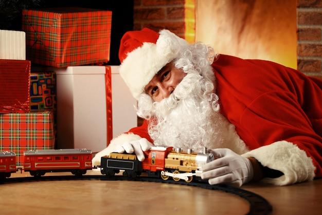 Kerstman spelen met speelgoed onder de kerstboom