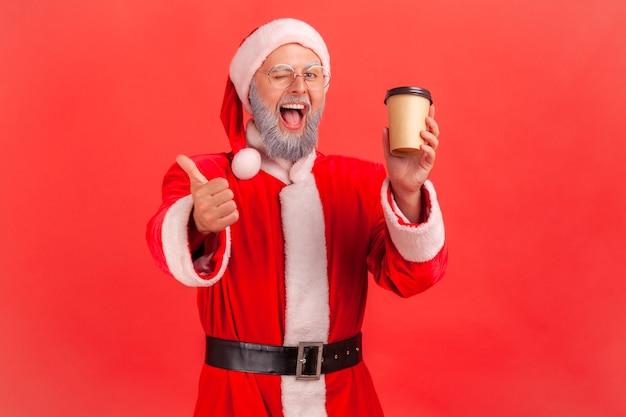 Kerstman staat met wegwerp papieren beker met koffie, duim opdagen.