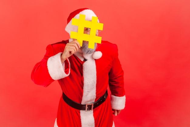 Kerstman verbergt gezicht achter hashtag-symbool, populaire blogger die aanbeveelt om tag, opmerkingen te volgen.
