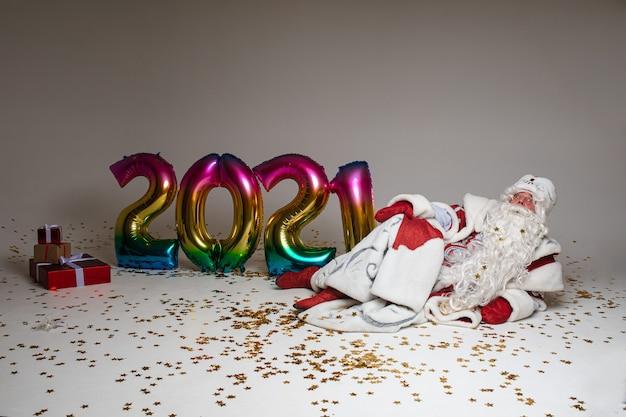 Kerstman viert kerstmis en 2021 nieuwjaar tot op de vloer met geschenken, ballonnen en confetti