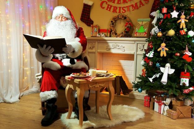 Kerstman zit met boek in een comfortabele stoel bij de open haard thuis