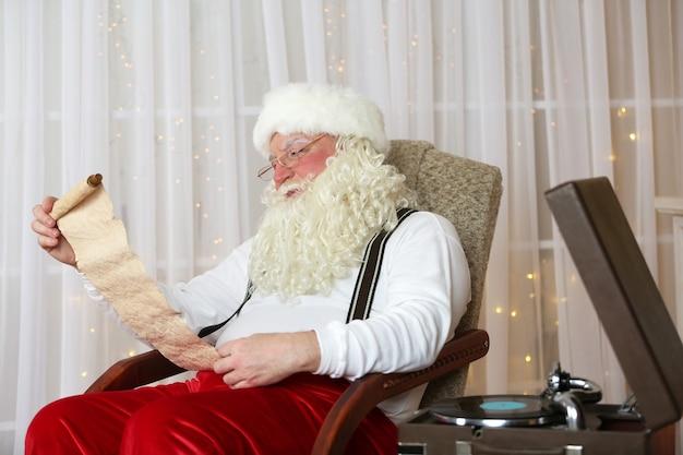 Kerstman zit met een lijst met kinderwensen in een comfortabele stoel bij de open haard thuis