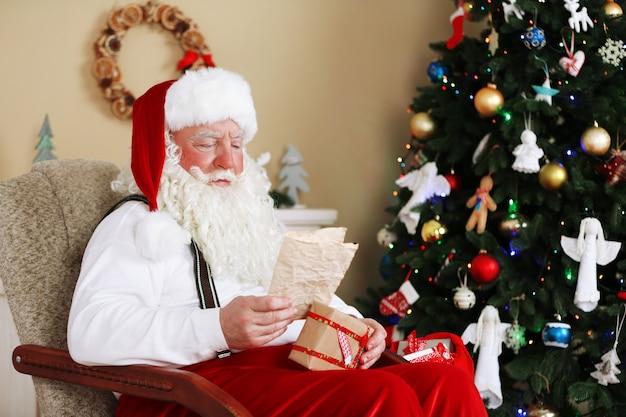 Kerstman zit met kinderbrieven in een comfortabele stoel bij de open haard thuis