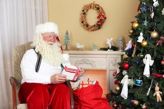 Kerstman zit met kinderen presenteert in een comfortabele stoel bij de open haard thuis