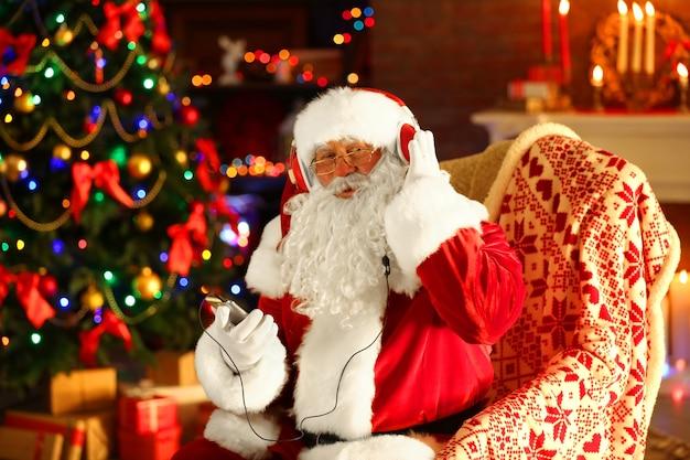 Kerstman zit met koptelefoon zittend in comfortabele schommelstoel thuis