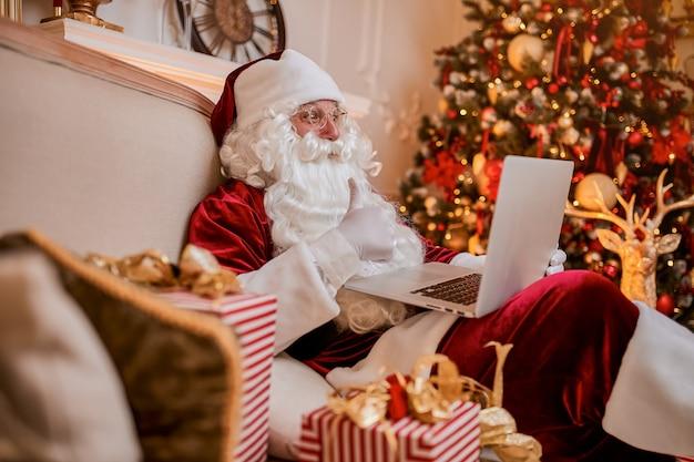Kerstman zit thuis en leest e-mail op laptop met ñ kerstverzoek of verlanglijstje bij de open haard en boom met geschenken. nieuwjaar en vrolijk kerstfeest, gelukkig vakantieconcept