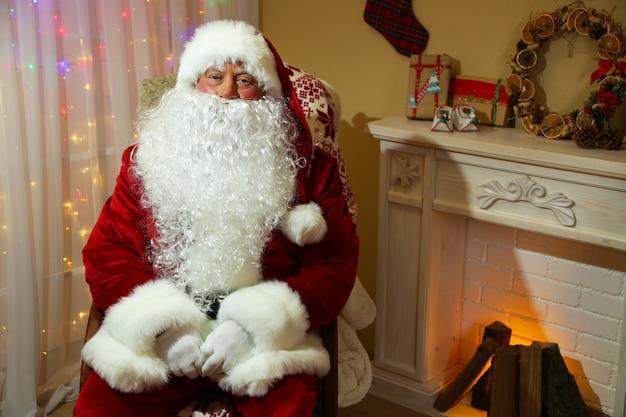 Kerstman zittend in een comfortabele stoel bij de open haard thuis