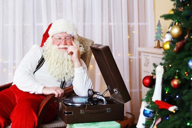Kerstman zittend in een comfortabele stoel in de buurt van retro draaitafel thuis
