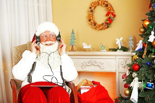 Kerstman zittend met digitale tablet in comfortabele stoel bij open haard thuis