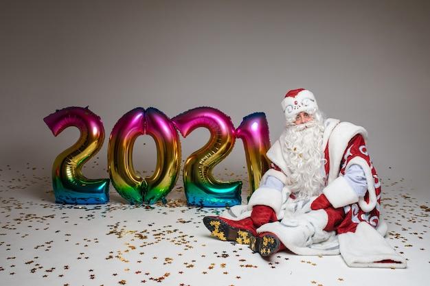 Kerstman zittend op de vloer met kleurrijke ballonnen in 2021-vorm, fotografie voor kerstmis en nieuwjaarsreclame