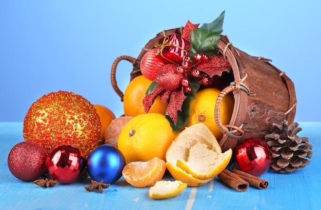 Kerstmandarijnen en kerstspeelgoed in mand op houten tafel op blauwe achtergrond