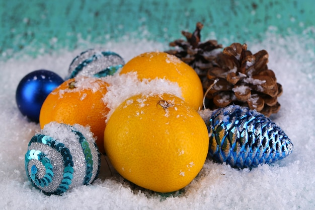 Kerstmandarijnen en kerstspeelgoed op houten tafel op sneeuw