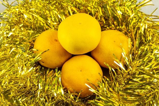 Kerstmandarijnen omgeven door geel klatergoud. kerst en nieuwjaar decoratie.