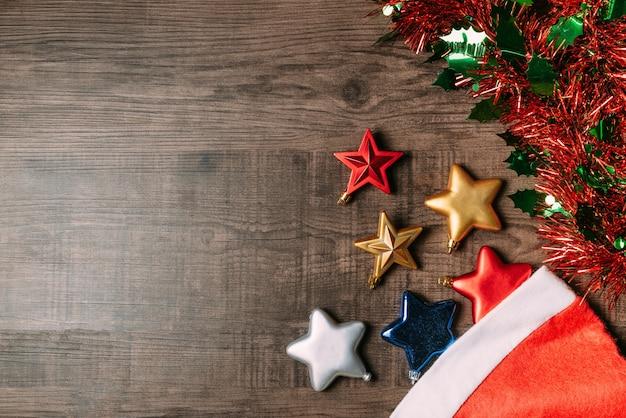Kerstmanhoed met metaalsterren en ornament op houten achtergrond.