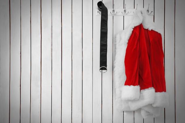 Kerstmanjasje en riem op een houten witte muur