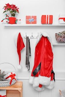 Kerstmankostuum die op witte muur hangen. ingerichte kerstkamer.