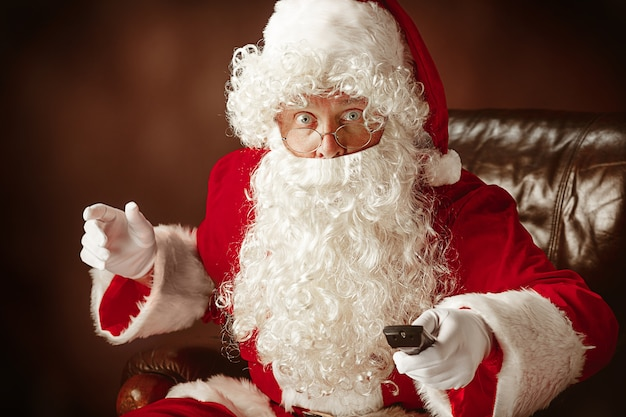 Kerstmankostuum met een luxe witte baard, kerstmuts en een rood kostuum op een rode studioachtergrond