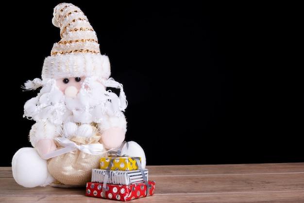 Kerstmanpop naast geschenkdozen.