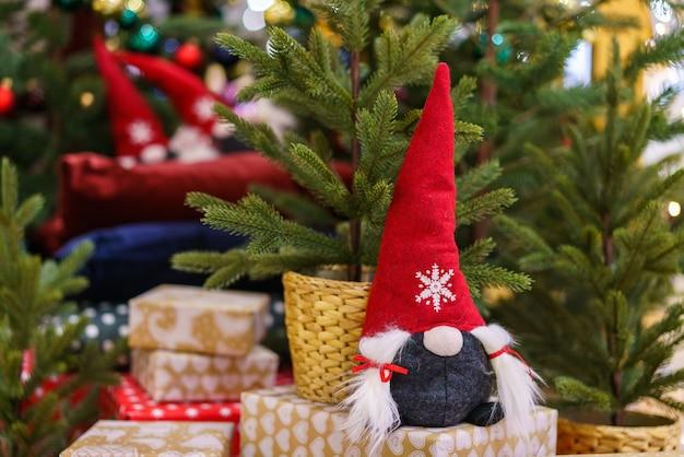 Kerstmanspeelgoed op de achtergrond van een kerstboom met geschenken kerststemming handgemaakt item voor decorati...