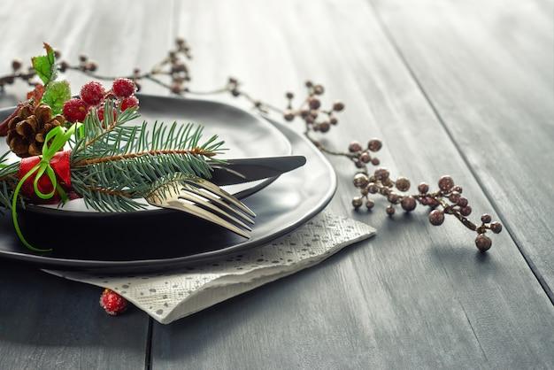 Kerstmenu concept met versierde zwarte borden en bestek