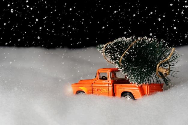 Kerstmis achtergrond. een auto rijdt in een kerstboom op een besneeuwde nacht. fijne kerst en nieuwjaar.