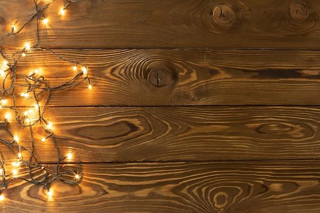 Kerstmis achtergrond. gloeiende slingers op bruine houten planken, één kant. ruimte kopiëren, plat leggen, bovenaanzicht. vakantie, kerstmis, nieuwjaar, feestconcept, lay-out met plaats voor tekst. horizontaal.