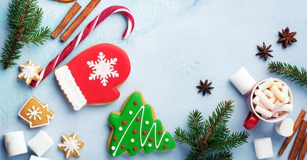 Kerstmis achtergrond. groep peperkoeken, kaneel, sinaasappel, speelgoed en kop warme chocolademelk op lichtblauwe achtergrond. selectieve aandacht. bovenaanzicht. ruimte kopiëren